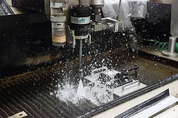 ノズルから勢いよく噴き出すウォータージェットの噴流。超高圧の水は金属も切断する。