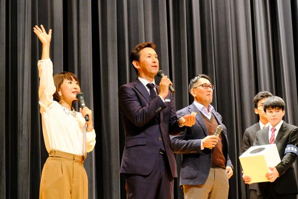 当選番号を読み上げる山内さん。住本さんも当選者探しをアシスト「当たった人は手を上げて~!」