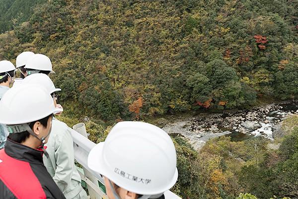 建設の作業場から70mほど下を流れるのが錦川。写真右側の小さな滝の箇所から、山を貫いて下流に通じるトンネルが現在掘られています。コンクリート打設ができるよう一時的に流れを変えるためで、転流工と呼びます。一時的とは言っても、高さ10m・長さ430mに及ぶ、一般道並みのトンネルになります。