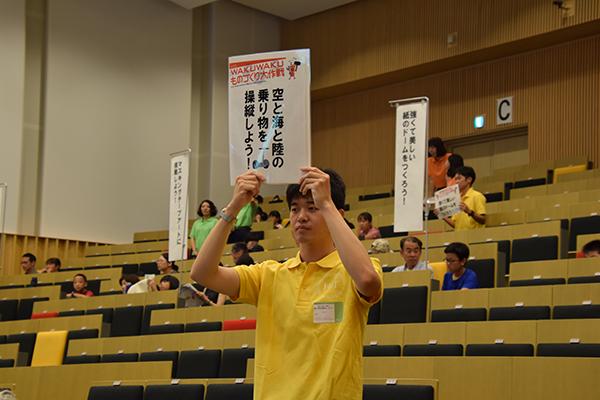 開会式が行われるデネブホールに続々と集まる参加者たち。学生たちが講座名の書かれたプラカードを持って誘導します。