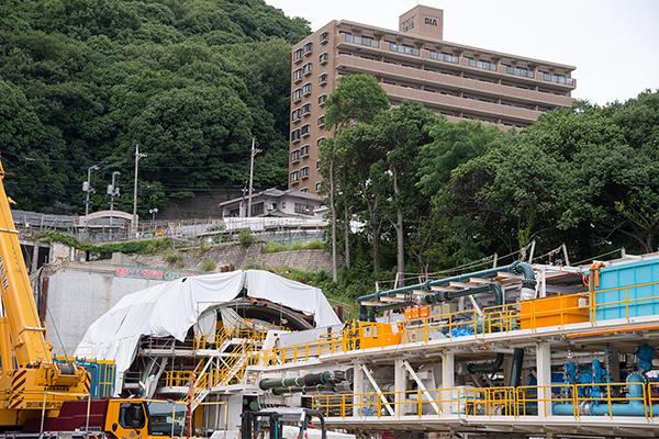 広島駅北口側のトンネル工事の様子を撮影。写真下左の白いカバーをかけられているのがシールドマシンです。工事現場のすぐ上(写真上右)には、マンションが建っています。上部に住居が密集しているため、シールド工法が選ばれたのです。