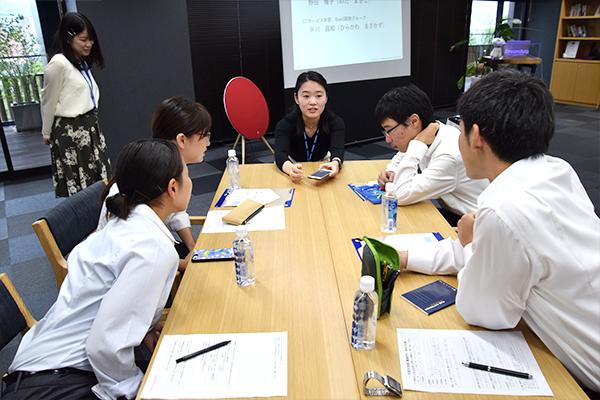 開発した自社システムをスマートフォンで見せながら若手社員が解説。広島工大のOBも開発に携わっているとのこと。