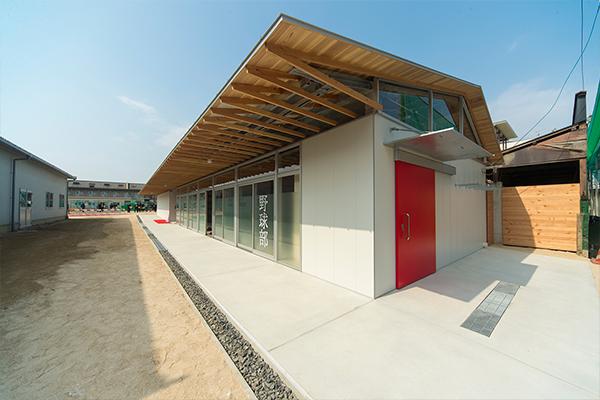 完成した野球部・弓道部の部室。「大屋根」の名にふさわしい大きな屋根は、ひさしの部分が長くなっています。雨が降っても部室前の通路を自由に通過でき、出入口も全部開放できるよう配慮されています。