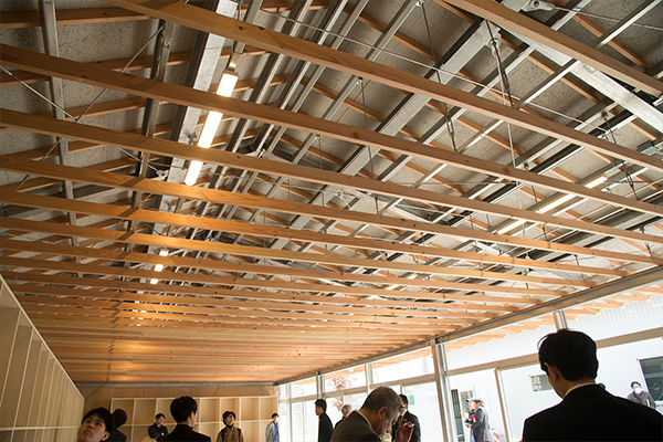 ※写真1部室の内部から天井を見上げると、こんな感じ。木製のルーバーと鉄骨で屋根を支えているのがわかります。木製のルーバーが、光に柔らかさと温かみを与えます。
