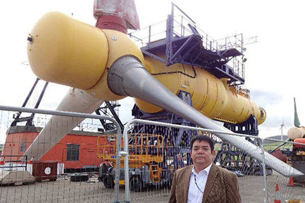 潮流発電システムを視察するためスコットランドを訪れた時の石垣先生。後ろに写っているのは、海底に設置する「着床式」の潮流発電システム。ブレードが約16ⅿもあり、大きな発電量を期待できますが、製造、設置、メンテナンスとも莫大なコストがかかってしまいます。そこで石垣先生のチームは、1機あたりの発電量は小さいけれど、コストが大幅に削減できる小型軽量潮流発電システムについて研究しています。