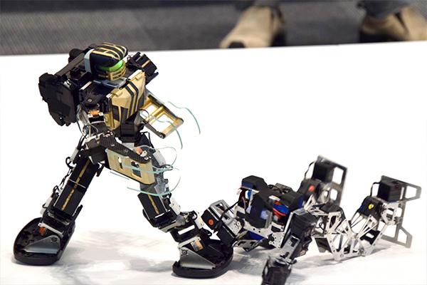 会場入口では、学生による二足歩行ロボット競技「ROBO-ONE」の実演が行われ、多くの来場者が対戦を見学されていました。