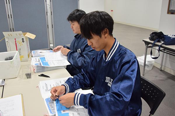 こちらは受付で配付資料を準備中。パンフレットと抽選券、アンケート用紙を一つひとつ手作業でセットしていきます。