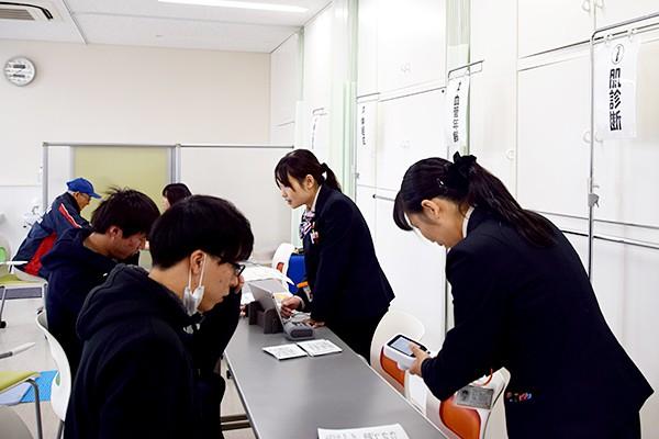健康チェックを受ける学生たち。どんな結果が出るのか、少し緊張した様子。