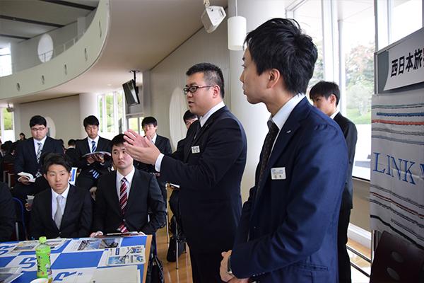 事業を説明する江角さん(奥)と白木さん(手前)。白木さんは広島工大OBで、学生たちの素朴な質問に丁寧に答えてくれました。