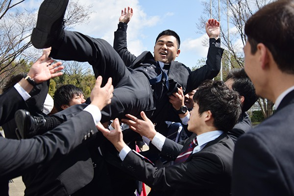 胴上げで派手に卒業生を祝福するラグビー部。