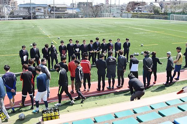 サッカー部は、思い出の練習場所「グリーンフィールドH.I.T」に集まり、在学生たちがメッセージ入りの色紙と花束を手渡していました。