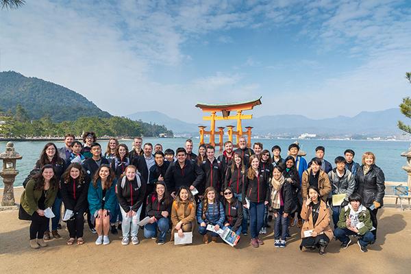 大鳥居がよく見える御笠浜で、みんな揃って記念撮影。TWU生は赤のラインが入った揃いの上着を着ています。演奏旅行に使用する合唱団のユニフォームだそうです。