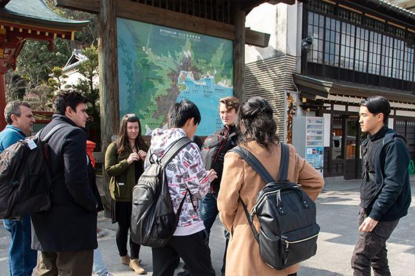 厳島神社の参拝を終えた後、宮島の案内板を前に次はどこへ向かうか相談する一行。「大元公園ってところに行ってみたいな」「それは遠いな」「大丈夫!早足だから」と話がまとまったようです。