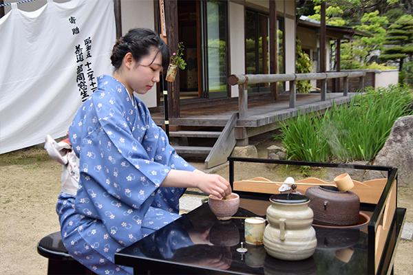 あでやかな着物姿でお点前を披露する女子学生。日本庭園を眺めながらの茶会は、ふれあいフェスタならでは。
