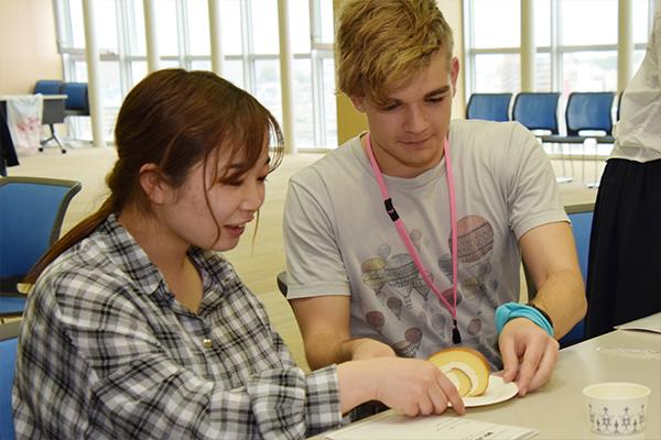 お菓子やケーキ、ジュースを囲んで歓談がスタート。レディファーストでスマートにケーキを渡す留学生。