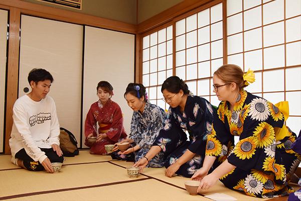 「お茶碗を手に持って右に回してください」と、茶道部員がお手本を見せながら作法を教えます。留学生たちも後に続き、見様見真似で実践。