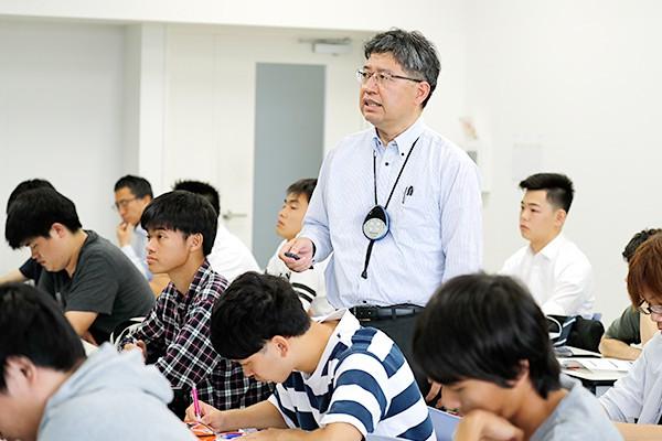学生の間を歩いて講義する久保川先生