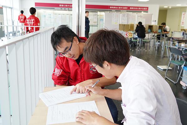 赤いジャンパーを着た学生自治会献血会のメンバーが呼び込みや問診票の記入をサポート。献血者をスムーズに誘導します。