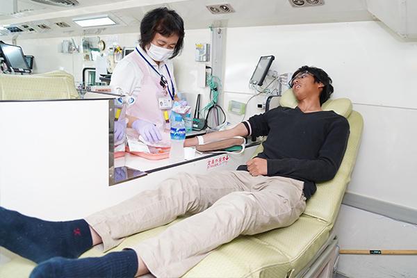 献血バス内で献血を受ける学生。看護師さんが体調を気にかけながら行ってくれるので、初めての方でも安心して受けられます。