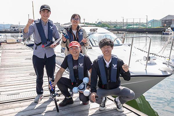 レンタルの小型クルーザーで江波沖から宮島へと出発する4人。各人の手には、実験に欠かせない器具が握られています。