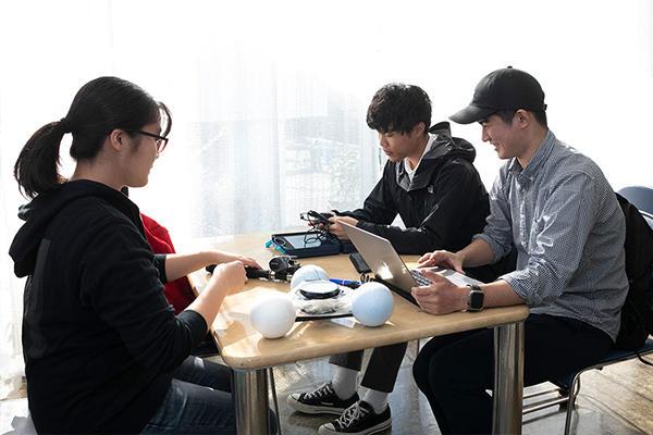 船に乗り込む前に、持参した実験器具の再確認を行う学生たち。左から松本亜弓さん、河内洸貴さん、砂田朋輝さん。ともに情報工学科・濱崎ゼミの4年生です。