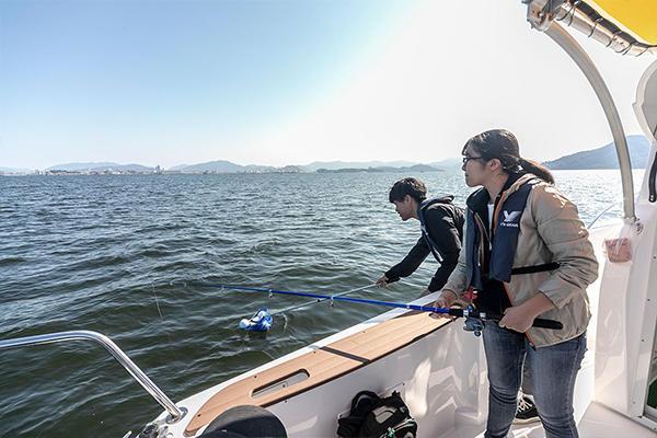 クローバーブイを網に乗せ、静かに海面へと浮かべます。