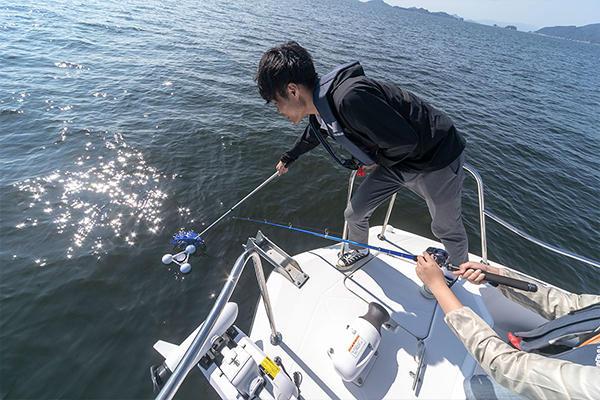 観測が終了すると、釣り竿のリールを巻いてブイを近づけ、最後は網ですくいます。内部の電子機器を壊さないよう、慎重に。