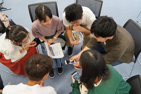 時にはスマートフォンで撮った写真を見せながら解説。参加学生たちは身を乗り出して話に聞き入ります。