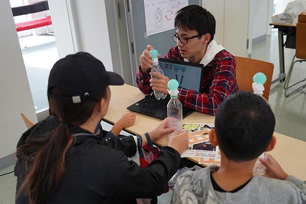 地球環境学科の学生が来場者と一緒にペットボトルを使った実験を行い、気圧の変化で雲ができる仕組みを説明。