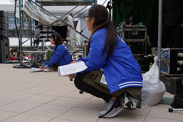 ステージ袖では、企画チームが台本を確認しながら進行を見守ります。