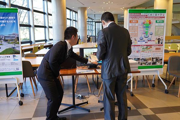 会場には7工大の展示ブースも設置。本学のブースでは来場者に学生がスライドを使って紹介していました。