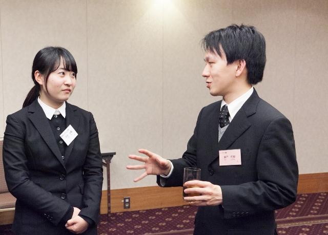 卒業生との懇親会で熱心に話を聞く坪田さん(左)